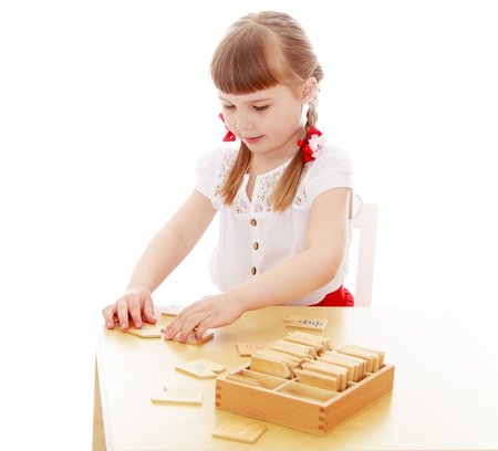 montessori: Keen little girl sits at a table in a Montessori kindergarten. The girl lays wooden cards in front of him-Isolated on white background Stock Photo