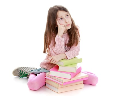 about age: Pensive little girl of school age sitting on the floor leaning on a stack of books. The girl looks in the Top about something dreaming-Isolated on white background Stock Photo