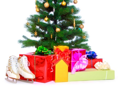 packaged: Beautifully decorated Christmas tree with Golden decorations and snowflakes on the branches. Around the tree are beautifully packaged gift boxes beside boxes are figure skates-Isolated on white background