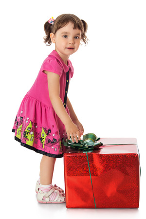 gifting: Lovely little girl near a Big box which is a gift-Isolated on white background