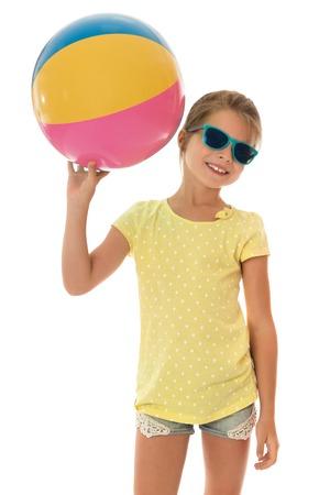 bola de billar: La niña en edad escolar en gafas de sol, pantalones cortos y una camiseta amarilla con mangas cortas que sostienen la pelota. Niña jugando voleibol con sus pares en la playa aislada contra el fondo blanco