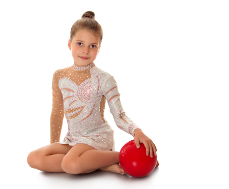 little girl posing: Beautiful young gymnast in a beautiful sports swimsuit sat on the floor . The girl holds the hand of a red ball.-Isolated on white background
