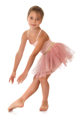 single child: Charming ballerina child of school age in a short pink dance dress -Isolated on white background