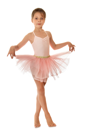 ballerina costume: Charming ballerina child of school age in a short pink dance dress , standing on toes and keeps the edges of the skirt fingers-Isolated on white background