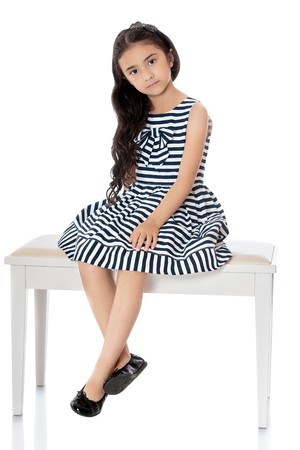 dangling: Fashionable little dark-haired girl dressed in a striped summer dress sat down on a white couch, dangling with his feet-Isolated on white background Stock Photo