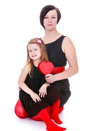 love expression: Fashion Mom and daughter in black dresses and red tights sat down on the floor. Mommy holds in his hand a box in the shape of a heart.-Isolated on white background Stock Photo