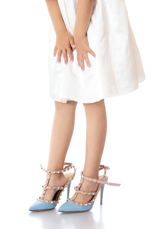 high heel shoe: Closeup of legs of a little girl are wearing oversized shoes.-Isolated on white background Stock Photo