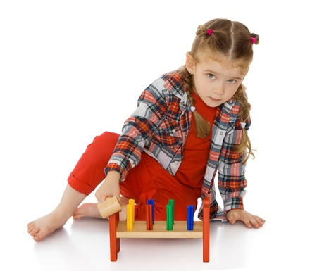 montessori: Cute little girl in red trousers and a shirt in a cage sitting on the floor and plays Montessori kindergarten-Isolated on white background