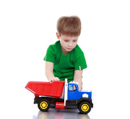 floor machine: Cute little boy playing with a big plastic truck . The boy sits on the floor-Isolated on white background