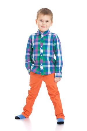 legs apart: Ni�o rechoncho en pantalones de color naranja y una camisa a cuadros. Un ni�o est� de pie con las piernas separadas y mantiene su mano en el bolsillo aislado en el fondo blanco