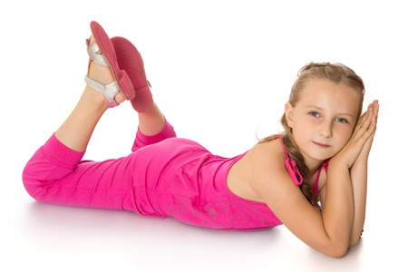 beautiful young girl in a pink jumpsuit, lying on the floor -Isolated on white background
