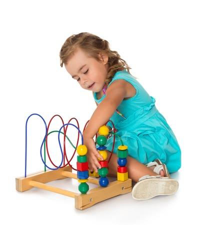Schattig klein meisje in Montessori kleuterschool zittend op de vloer en speelt - geïsoleerd op een witte achtergrond
