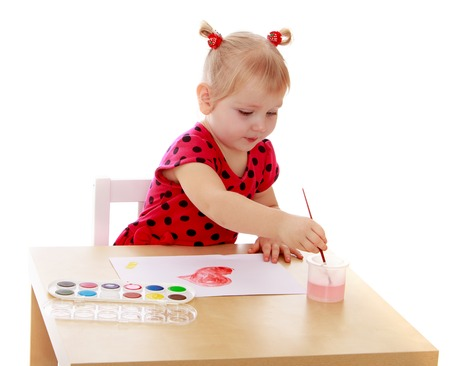 keen: Keen little girl sits at table and paints with watercolors. The girl dips the brush in a jar of water-Isolated on white background Stock Photo