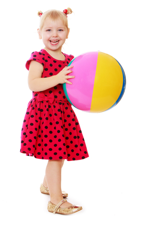 peers: Laughing little girl blonde in a long red dress with polka dots holds before itself big inflatable striped ball. Girl playing with their peers on the beach-Isolated on white background