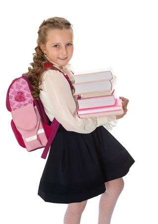 Joyful girl schoolgirl in a white blouse AI black long skirt carries a heavy stack of books-Isolated on white background Stock Photo