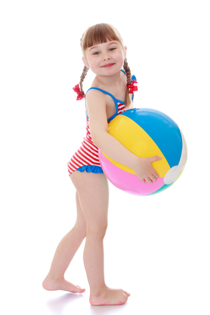 little girl swimsuit: Beautiful little blonde girl with short bangs and long braids are braided in red bows holding a large striped inflatable ball. Girl in a swimsuit, she is vacationing with his parents on the beach-Isolated on white background Stock Photo