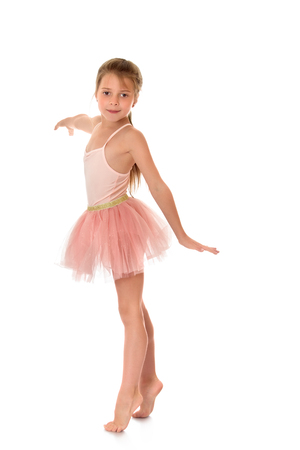 on tiptoes: Beautiful girl of school age in a pink dress ballerina. The girl opened his arms to the side and standing barefoot on tiptoes on the floor-Isolated on white background