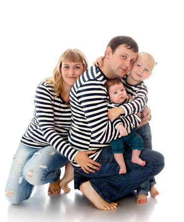 recently: Happy family of 4 people in the same striped shirts. Happy dad hugging along with their children, older charming young daughter, and the youngest , only recently born son. Hugs all and happy mom-Isolated on white background Stock Photo