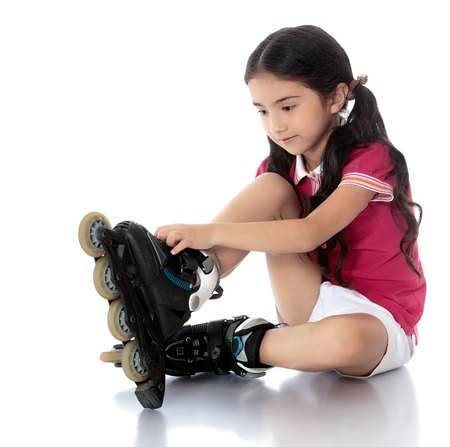 Adorable little dark-haired girl of Eastern appearance sitting on the floor and lock buttons on roller skates. Girl wearing pink top and short white shorts-Isolated on white background Фото со стока