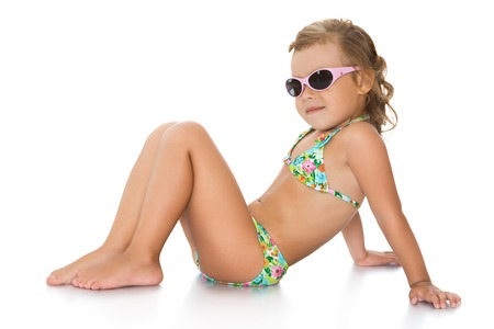 one little girl: Cute little girl in black sunglasses and a blue bikini is sitting on the floor , turning sideways to the camera-Isolated on white background Stock Photo