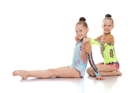 female child: Adorable, beautiful little girls gymnasts sit leaning on each other. Synchronous movement . The girls are dressed in a smart sports swimwear-Isolated on white background