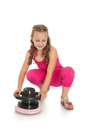 Cheerful girl of school age in a pink jumpsuit rubbing burnisher floor . the girl is cleaning up the school room-Isolated on white background