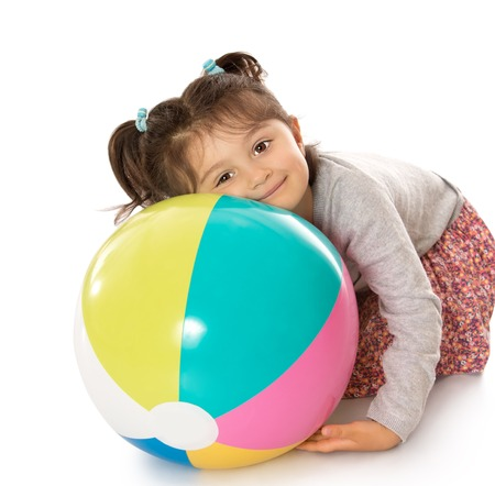 ball isolated: Happy little girl sitting on the floor with his head resting on a large inflatable striped ball-Isolated on white background