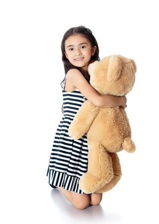 hugging knees: Beautiful Oriental girl of school age is on his knees hugging a Teddy bear-Isolated on white background