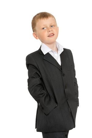 broadside: Fashion little blonde boy in a grey suit standing broadside to the camera . The boy stuck his hands in his pockets . Closeup-Isolated on white background