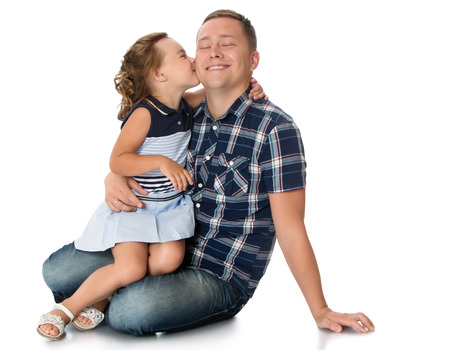 kids playing beach: Happy little girl sitting on dads lap and gently kisses him on the cheek. The priest closed his eyes He is very happy-Isolated on white background Stock Photo