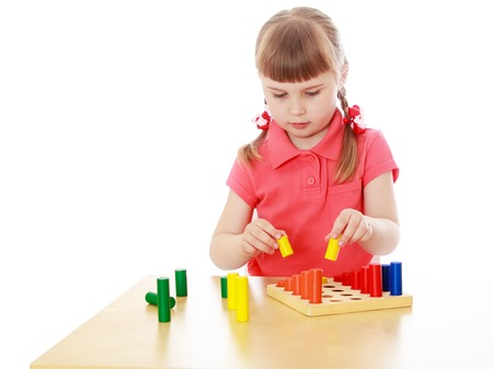 montessori: Cute little blond girl with short bangs and short pigtails on her head sitting at a table in a Montessori kindergarten . the girl is working with Montessori material-Isolated on white background