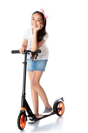 Mooi donkerharige meisje in een korte denim rok rijdt haar scooter.-Geïsoleerd op witte achtergrond