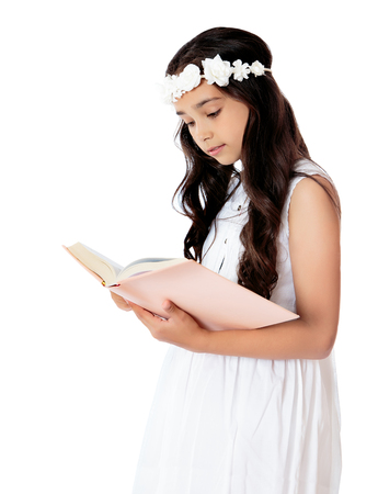 absorbed: Beautiful dark-haired girl in schoolgirl elegant white dress absorbed reading a book . The plan-Isolated on white background