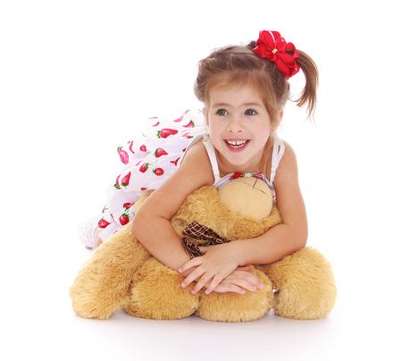 petite fille avec robe: Cute petite fille dans une robe blanche d'�t� l�gitime sur le sol et serrant un ours en peluche-Isol� sur fond blanc Banque d'images