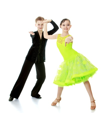 Boy and girl children dancing holding hands. Children are doing this ballroom dancing . Children dance the dance the cha-cha-cha-Isolated on white background Imagens