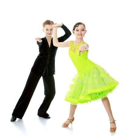 Jongen en meisje kinderen dansen hand in hand. Kinderen doen dit stijldansen. Kinderen dansen de dans de cha-cha-cha-Geïsoleerd op witte achtergrond
