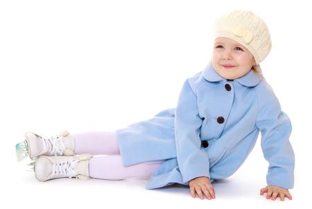 active girl: Cute little girl in white winter hat and coat golum sitting on the floor . on the feet of girls figure skates-Isolated on white background