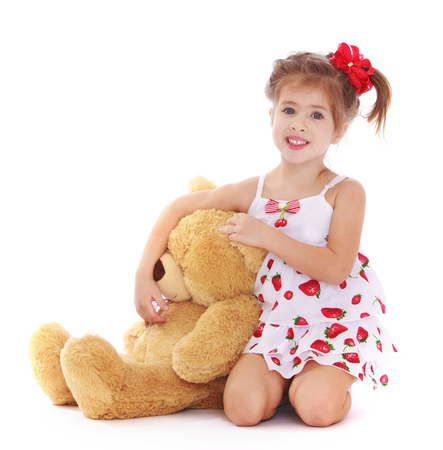 playing with spoon: Funny little girl in short white summer dress hugs a big Teddy bear . the girl is kneeling on the floor-Isolated on white background