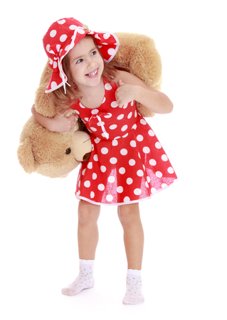 playing with spoon: Funny little girl in a short red summer dress with white polka dots and matching bonnet, holds on his shoulders a large Teddy bear . the girl is on the floor in white socks -Isolated on white background