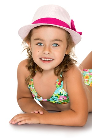 girl with camera: Beautiful little blonde girl in a blue swimsuit lying on the floor and smiling at the camera. The head girls pink hat. The plan-Isolated on white background