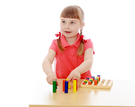montessori: Adorable little blonde girl with short bangs and tiny braids that are braided in red ribbons in a Montessori kindergarten. Girl playing at the table with Montessori material-Isolated on white background
