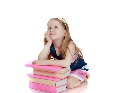 apparently: Thoughtful little blonde girl sitting on the floor leaning on the stack of books. The girl looks up apparently dreams of something-Isolated on white background