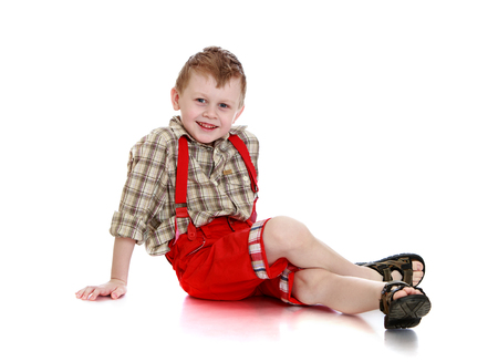 red shorts: Happy little blond boy in a plaid shirt and red shorts with straps sitting on the floor leaning on hands-Isolated on white background