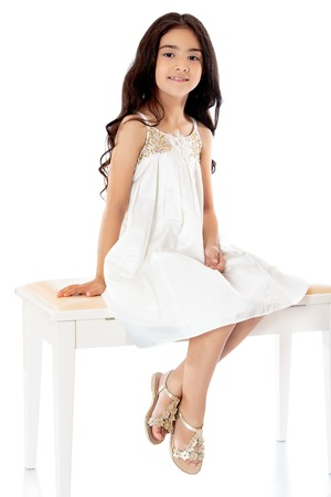 black hair: Fashionable dark-haired little girl in a beautiful beige dress sitting on white couch with his feet dangling. -Isolated on white background