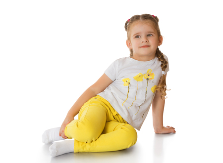 pantalones abajo: Niña rubia feliz en pantalones amarillos y una camiseta blanca se sentaron en el suelo aislado sobre fondo blanco Foto de archivo