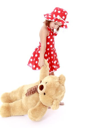 playing with spoon: beautiful little Caucasian girl in a short red summer dress, and hat with polka dots pulls the paw of a big Teddy bear - Isolated on white background