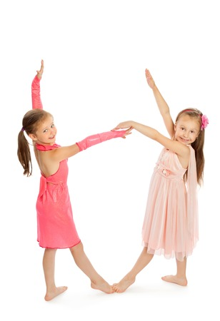facing each other: Small girl gymnast stand facing each other and holding hands-Isolated on white background