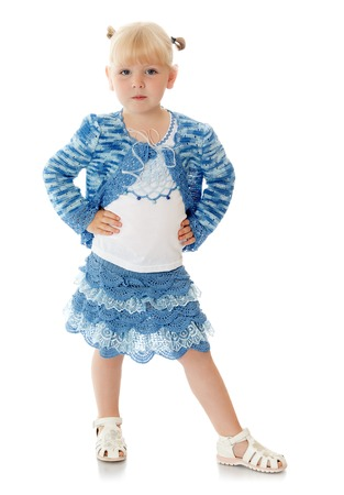 put forward: Fashionable little blonde girl in a smart knitted suit blue posing for the camera put a leg forward - Isolated on white background Stock Photo