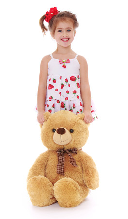 playing with spoon: Cute little girl in colorful white dress with a red bow on his head plays with big Teddy bear - Isolated on white background Stock Photo