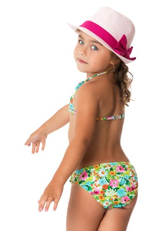 camera girl: Beautiful little girl in the pink hat and the swimsuit turned his back to the camera . Closeup - Isolated on white background